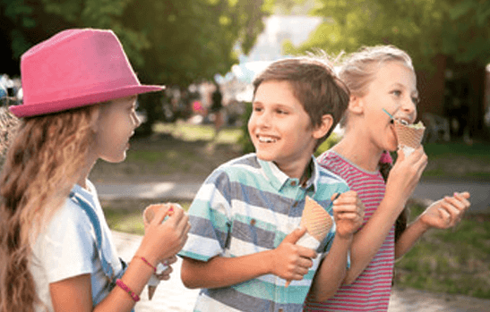 Kids smilling while eating ice-cream cones