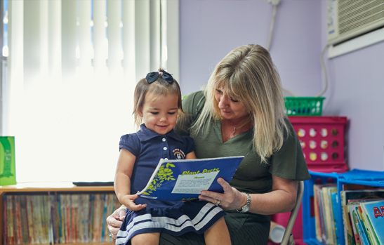 Rainbow Christian Academy teacher with a pre-k student on her lap while she reads her a story